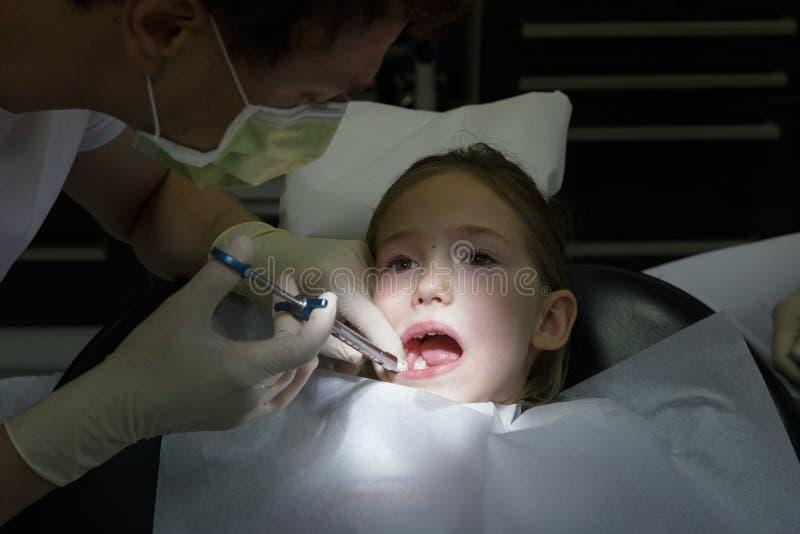 Skrämd liten flicka på tandläkarekontoret som får injektionen för lokal anestesi in i gummin, tandläkare som gör stel gummin för  arkivbild
