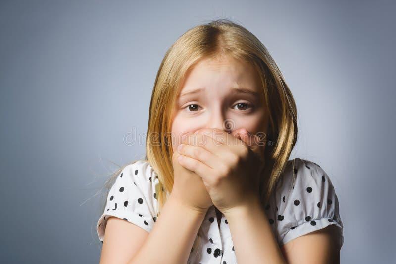 Skrämd och chockad liten flicka för Closeup Studioskottstående över grå bakgrund Mänskligt sinnesrörelseframsidauttryck livstid royaltyfri bild