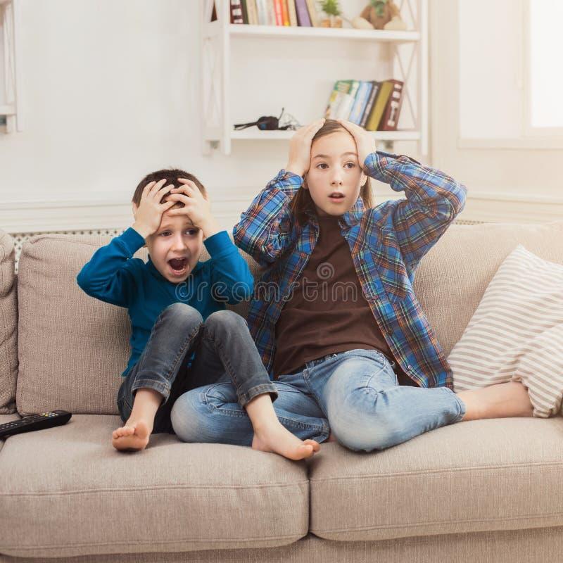 Skrämda barn som hemma håller ögonen på TV royaltyfri fotografi