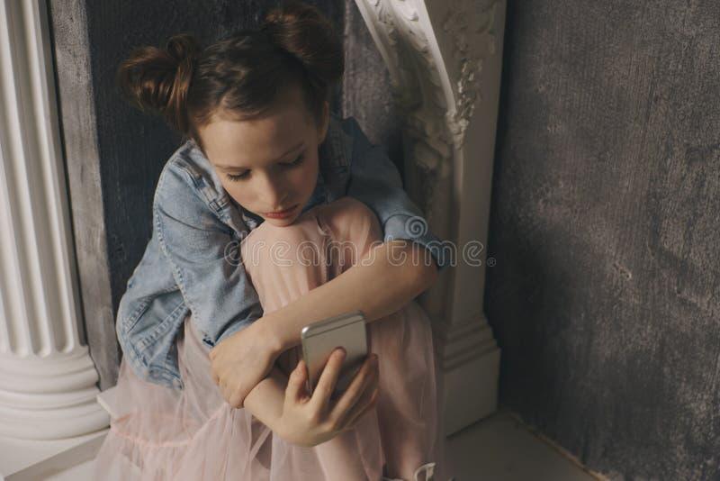 Skrämt barn och oroad hållande mobiltelefon för tonåringflicka, som internet förföljde det missbrukade offret och cyberbullying e royaltyfria foton
