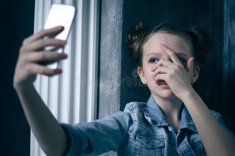 Skrämt barn och oroad hållande mobiltelefon för tonåringflicka, som internet förföljde det missbrukade offret och cyberbullying e royaltyfri foto