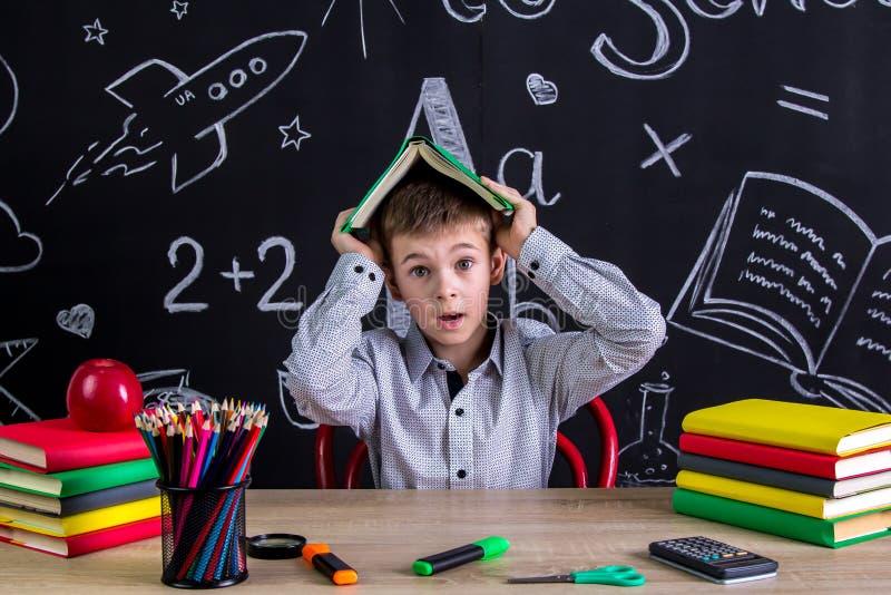 Skrämt och förbryllat skolpojkesammanträde på skrivbordet som rymmer boken ovanför huvudet som omges med skolatillförsel arkivfoto