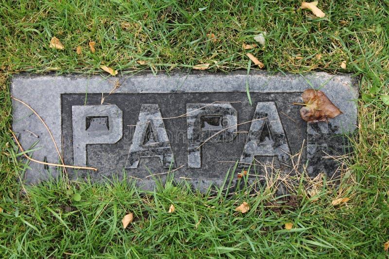 Skräp dolda Papa Marble Headstone i gammal kyrkogård royaltyfri fotografi