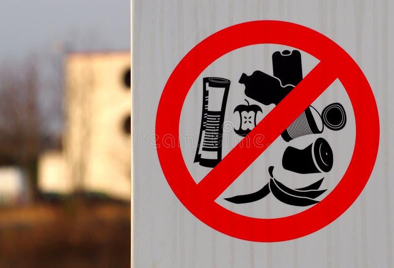 Skräpa ner inte tecknet med förbudsymbolen av symbolerna av bananen skalar, papper, plast- flaskor, på burk framme, plast- koppar arkivbilder