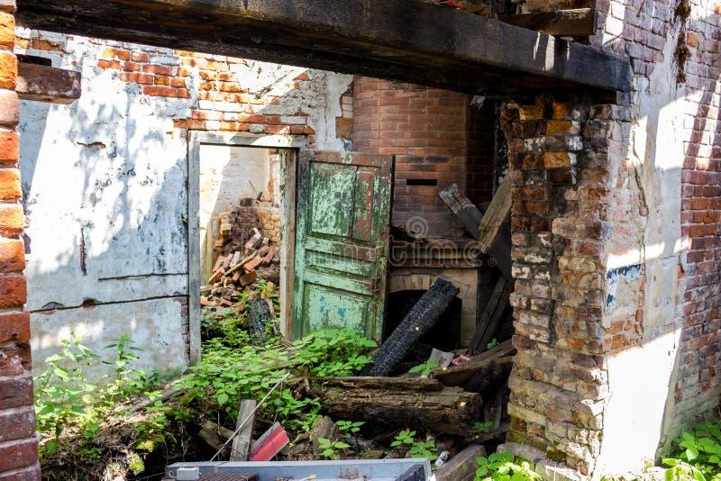 Skräpat ner rum av ett gammalt övergett hus, en bruten dörr och en gammal tegelstenspis fotografering för bildbyråer