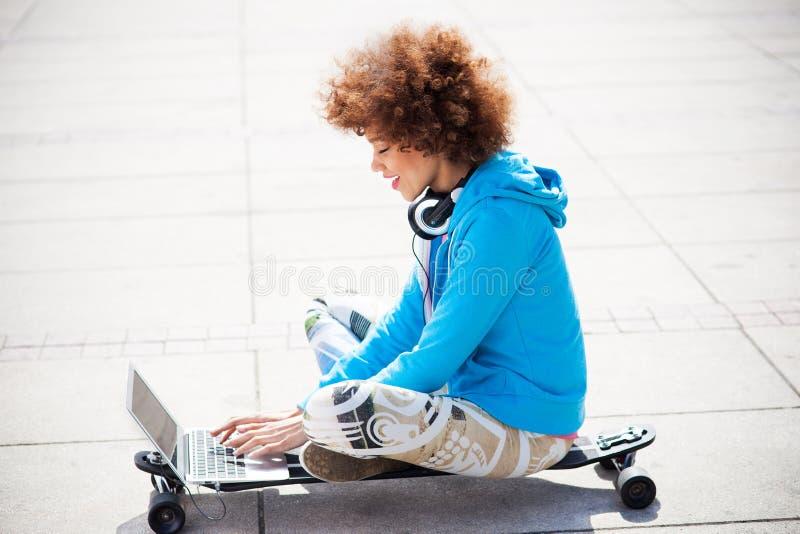 Skraj kvinnasammanträde på skateboarden med bärbara datorn arkivfoto