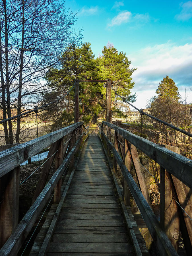 Skranglig bro som in kommer till Aberlour royaltyfria foton