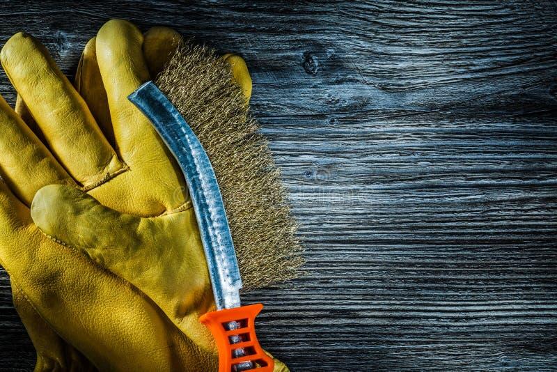 Skrapatrådborsten piskar skyddande handskar på tappning träb arkivbild