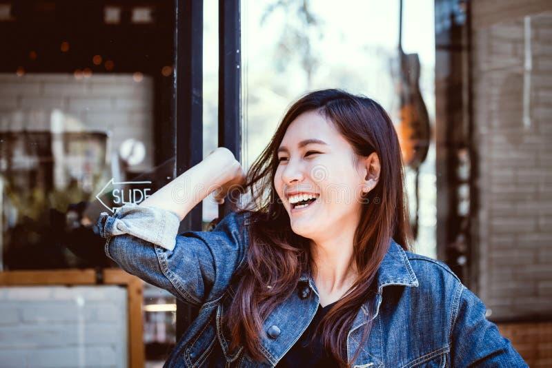 Skratt för tonårs- flicka för Asien ungdom på väggexponeringsglasbakgrund royaltyfri foto