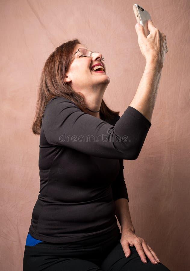 Skratt för vuxen kvinna, som hon rymmer mobiltelefonen arkivbild