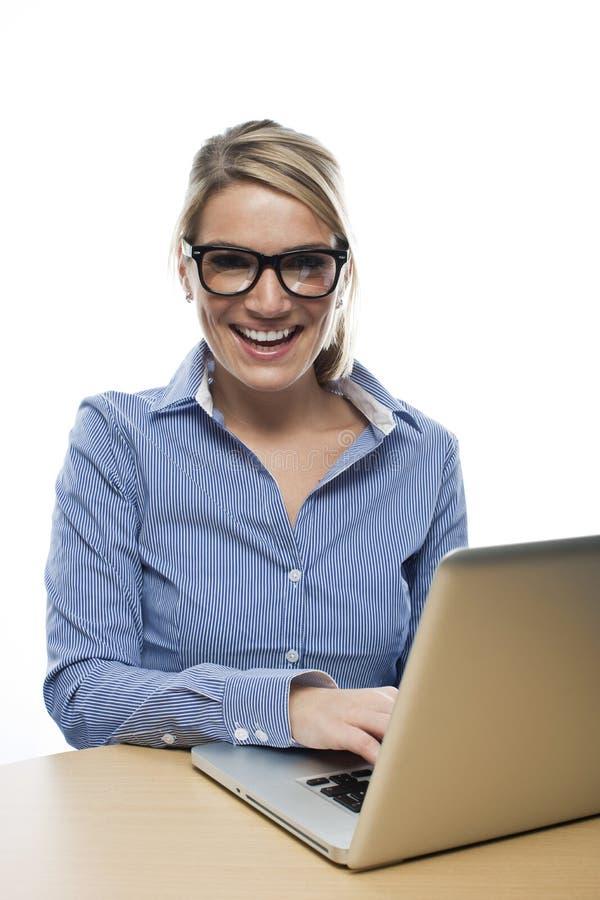 Skratta affärskvinnan som arbetar på hennes bärbar dator arkivbild