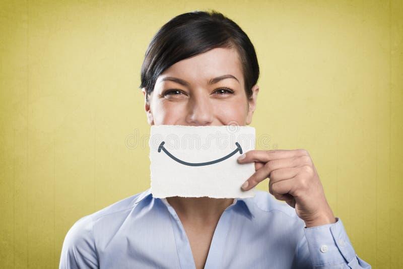 Skratta affärskvinnan som rymmer det tomma vita kortet främst av hennes mun royaltyfri bild