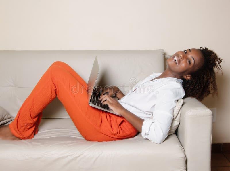 Skratta afrikansk amerikankvinnan med anteckningsboken på soffan fotografering för bildbyråer