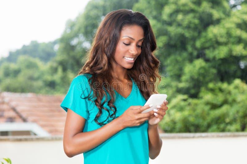Skratta afrikansk amerikankvinnan med lång hårmessaging med mo arkivbild