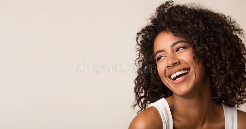 Skratta afrikansk amerikankvinnan som ser bort på ljus bakgrund arkivfoto