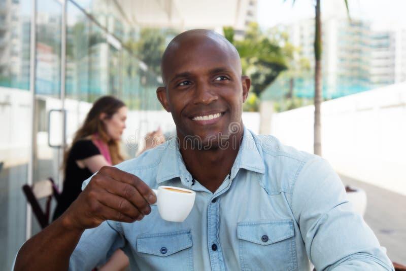 Skratta afrikansk amerikanmannen som tycker om en kopp kaffe arkivfoton