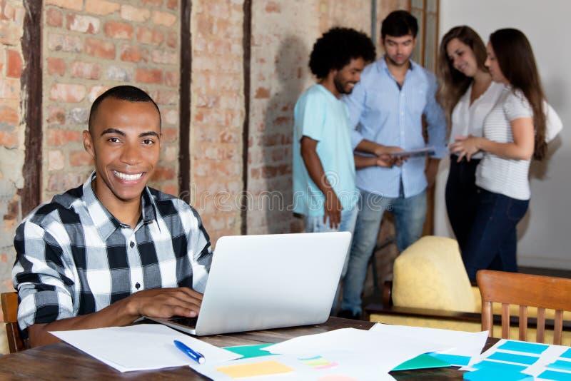 Skratta afrikansk amerikanprogramvarubärare på kontoret av compan royaltyfria foton