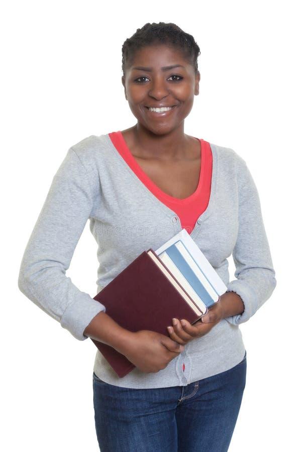 Skratta afrikansk amerikanstudenten med böcker arkivfoton