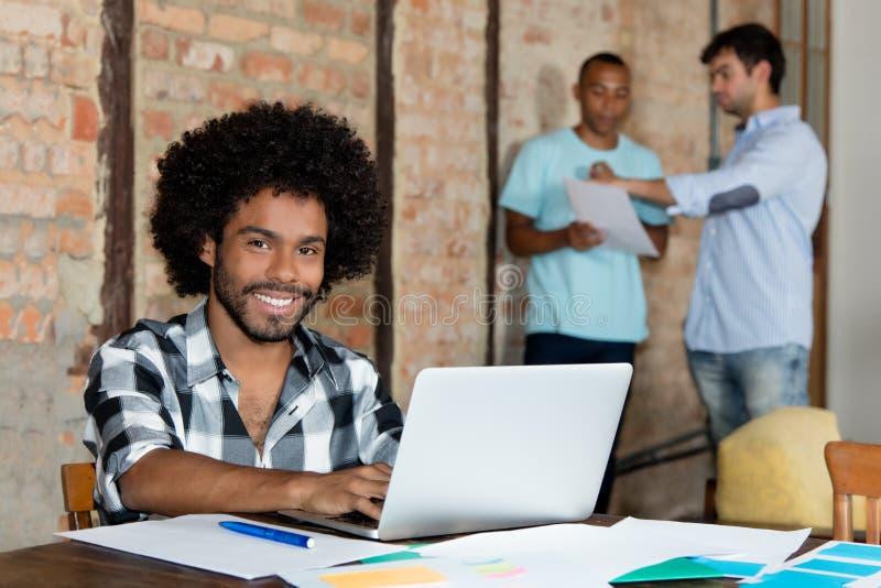 Skratta bärare för afrikansk amerikanhipsterprogramvara på datoren arkivfoto