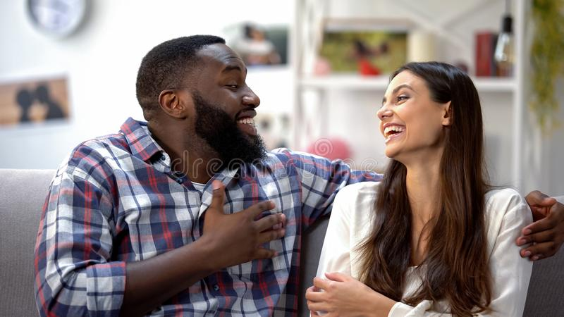 Skratta blandad-lopp par som skojar och att ha rolig konversation, samhörighetskänsla arkivfoton