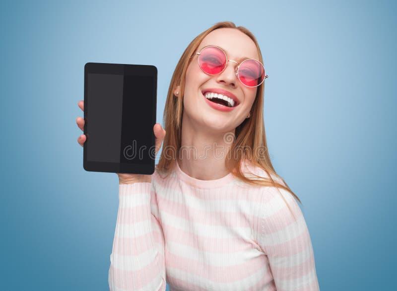 Skratta blondinen i rosa visningminnestavla royaltyfri foto