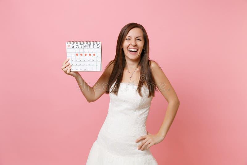 Skratta brudkvinnan i den vita bröllopsklänningen som rymmer den kvinnliga periodkalendern för att kontrollera på menstruationdag fotografering för bildbyråer
