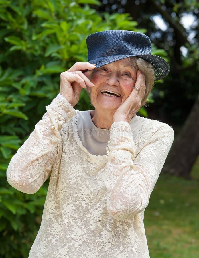 Skratta den äldre damen som bär en hatt arkivfoton