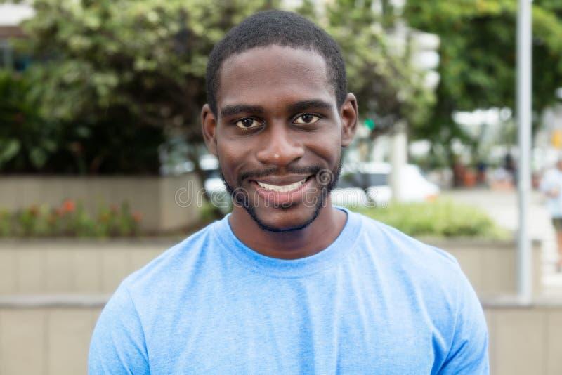 Skratta den afrikanska mannen med skägg- och blåttskjortan royaltyfri foto