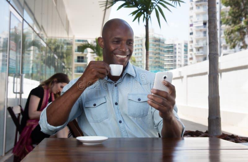 Skratta den afrikanska mannen som surfar internet med telefonen i en restaurang arkivfoto