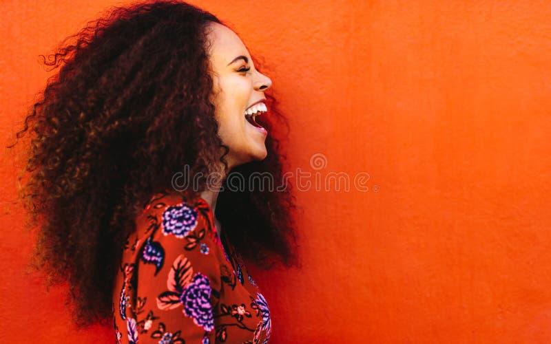 Skratta den afrikanska unga kvinnan med lockigt hår arkivbild