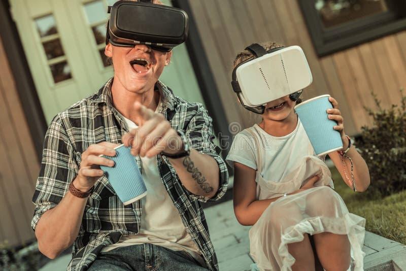 Skratta den aktiva fadern i den svartvita skjortan som spelar i VR-hjälm arkivbilder