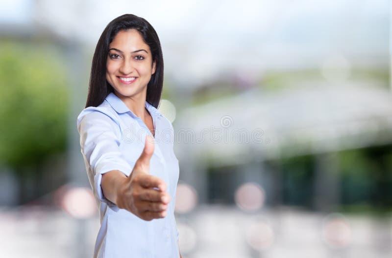 Skratta den arabiska affärskvinnan som når handen fotografering för bildbyråer