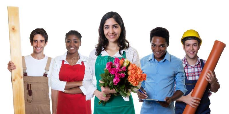 Skratta den arabiska blomsterhandlaren med gruppen av andra internationella lärlingar arkivbild