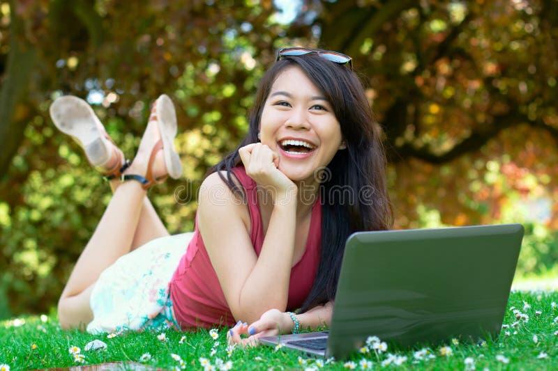 Skratta den asiatiska flickan på parkera arkivbilder
