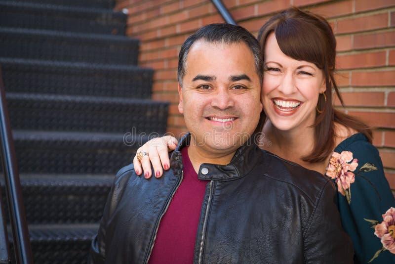 Skratta den Caucasian kvinnan för blandat lopp och den latinamerikanska mannen royaltyfri bild