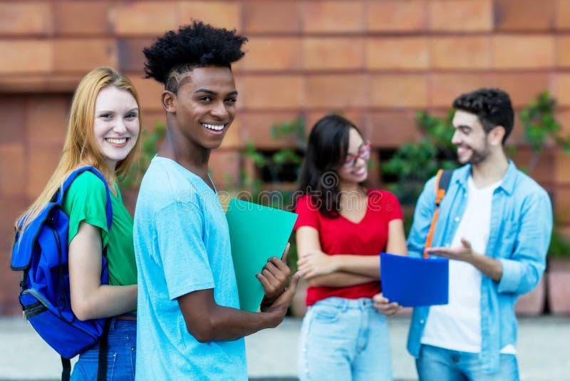 Skratta den caucasian manliga studenten för kvinnlig och för afrikansk amerikan royaltyfri fotografi