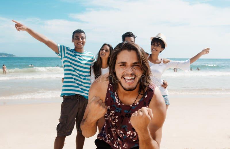 Skratta den caucasian mannen med unga vuxna människor för bifall på stranden royaltyfri fotografi