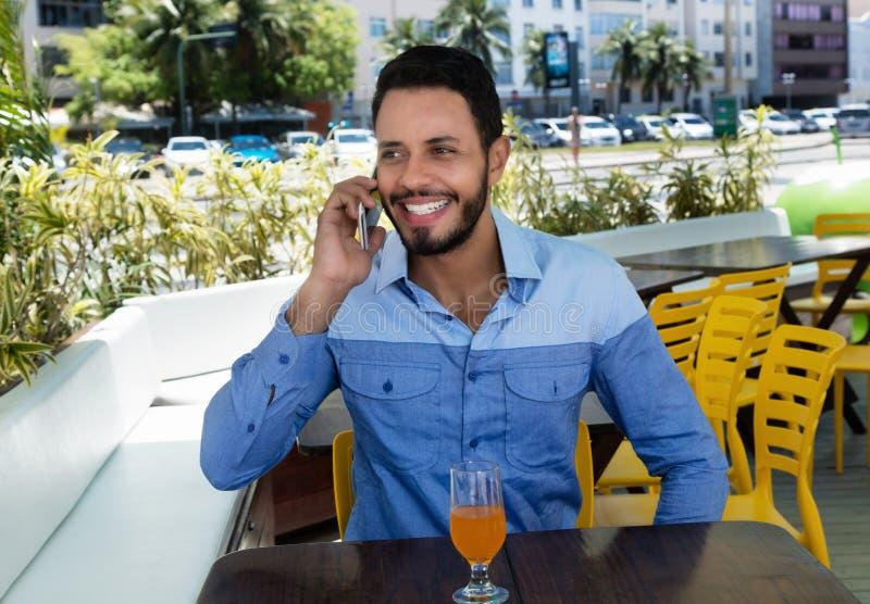 Skratta den caucasian mannen som talar på mobiltelefonen i restaurang royaltyfria bilder