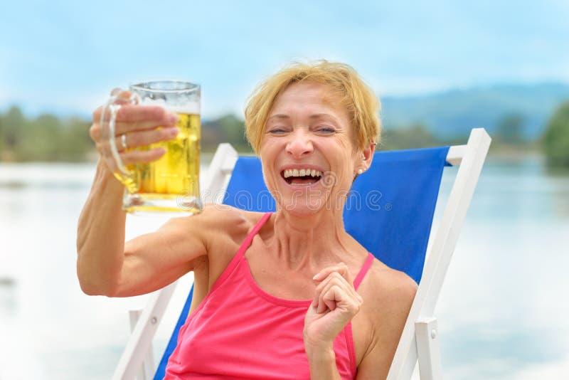 Skratta den glade kvinnan som rostar med ett öl arkivfoton
