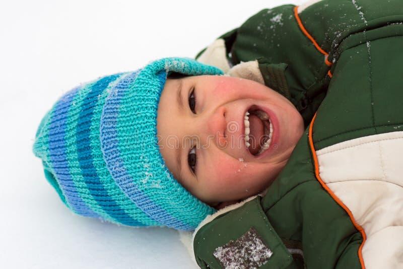 Skratta den gladlynta pojken på snö arkivfoto