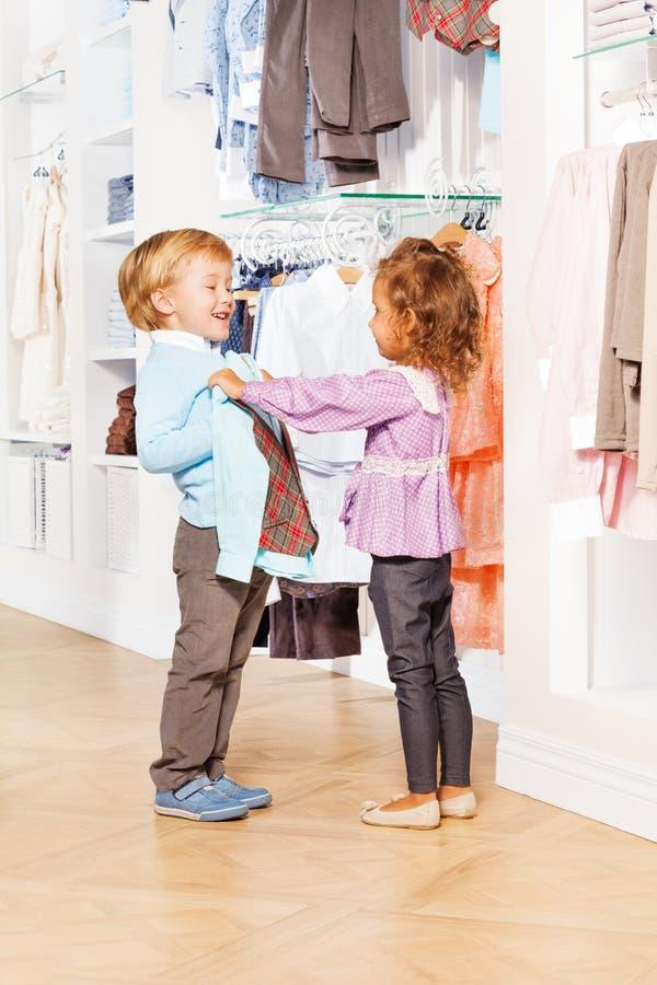 Skratta den gulliga pojken och flickan välj kläder tillsammans fotografering för bildbyråer