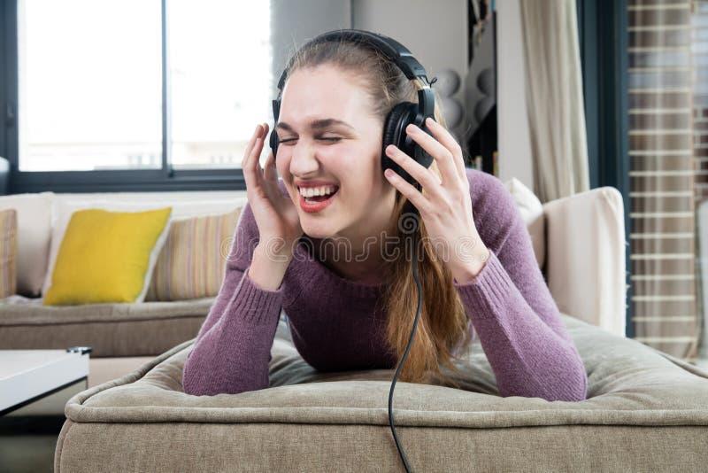 Skratta den härliga tonårs- flickan med hörlurar som lyssnar till rolig musik royaltyfria foton