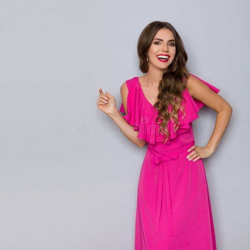 Skratta den härliga unga kvinnan i elegant rosa klänning royaltyfri bild