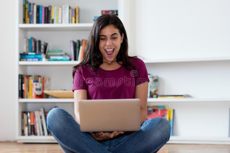 Skratta den indiska kvinnan som direktanslutet shoppar med datoren royaltyfria bilder
