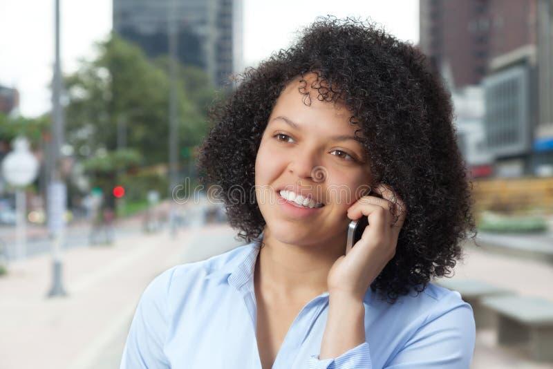 Skratta den latinamerikanska kvinnan i staden som talar på telefonen royaltyfri fotografi