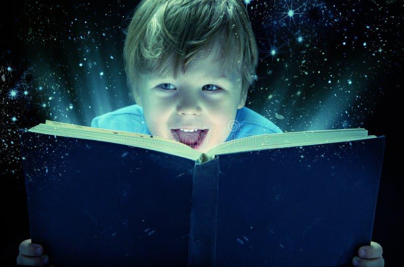 Skratta den lilla pojken med den magiska boken fotografering för bildbyråer