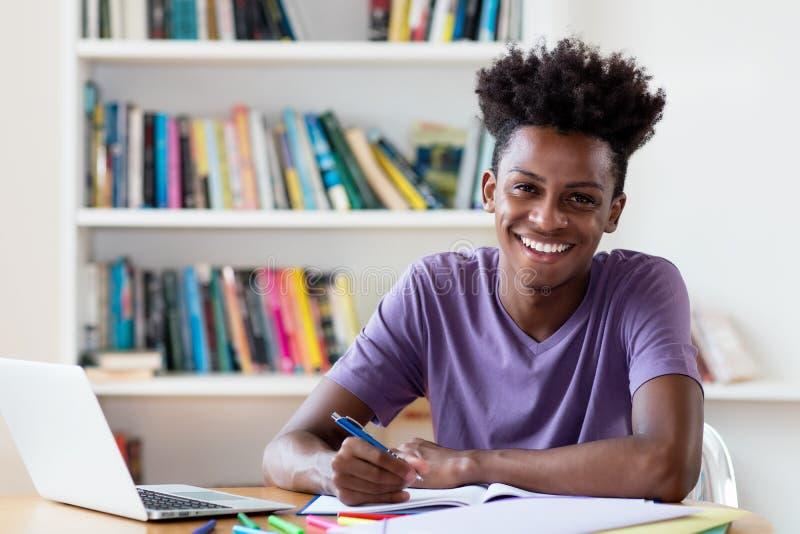 Skratta den manliga studenten för afrikansk amerikan som lär för diplom royaltyfri fotografi