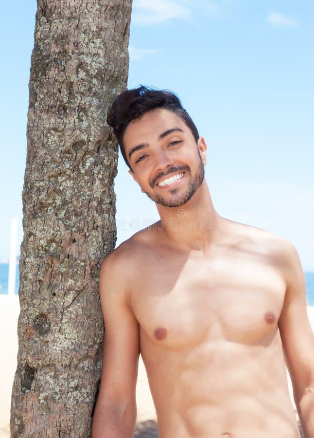 Skratta den muskulösa latinska grabben på stranden royaltyfria bilder