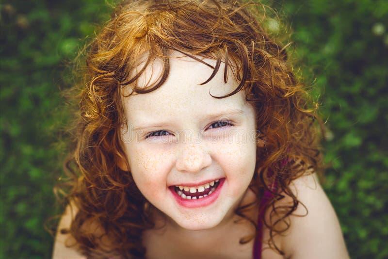 Skratta den redheaded lilla flickan med fräknar arkivfoto