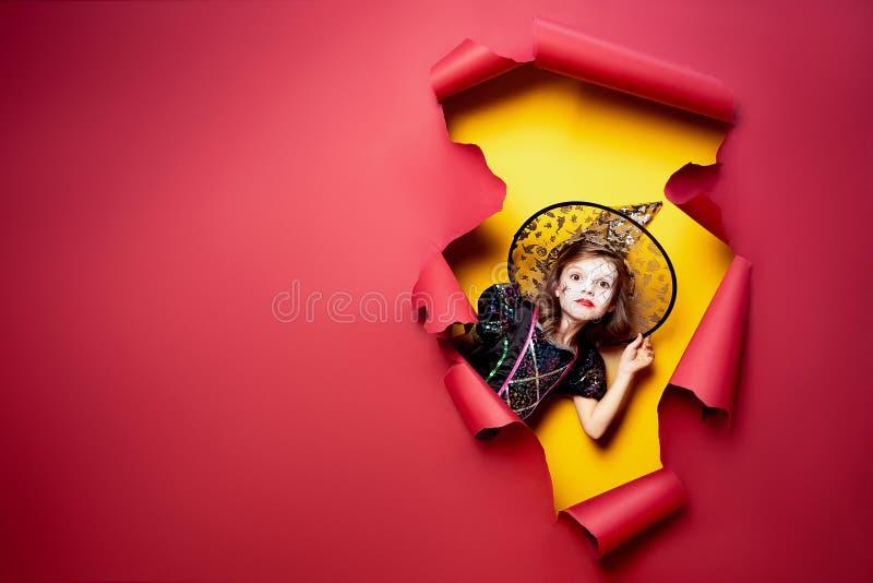 Skratta den roliga barnflickan i en häxadräkt i halloween royaltyfria bilder